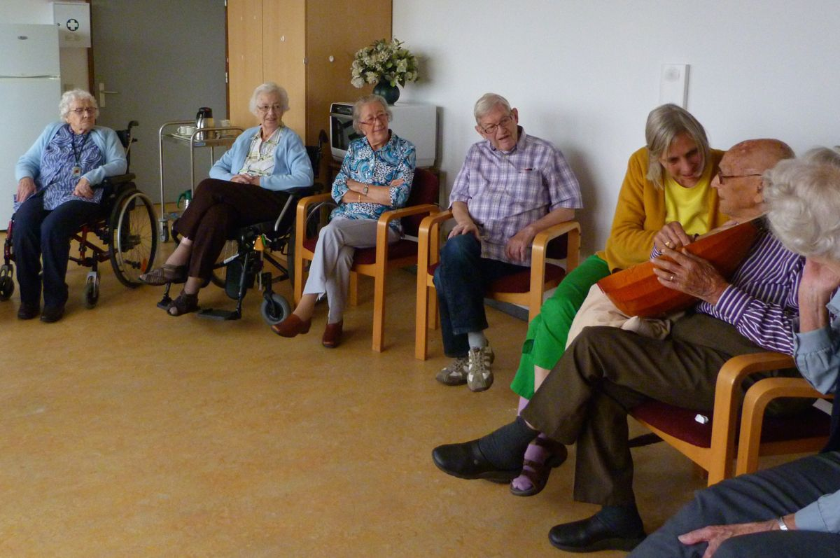 photo, residents from elderly people's home Transwijk look attentively how mister Oostrom enjoys playing the lute, Utrecht, 21 September 2012